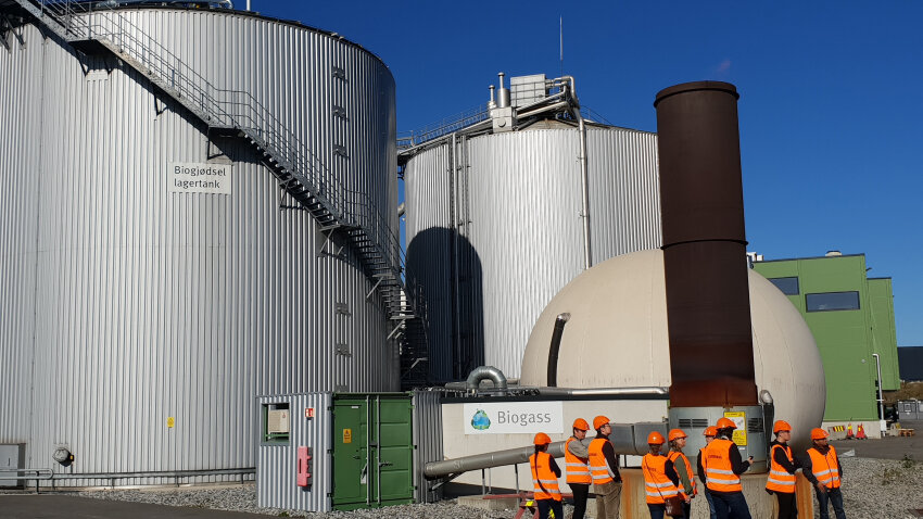 Workers in orange vests outside of metal silos for biogas
