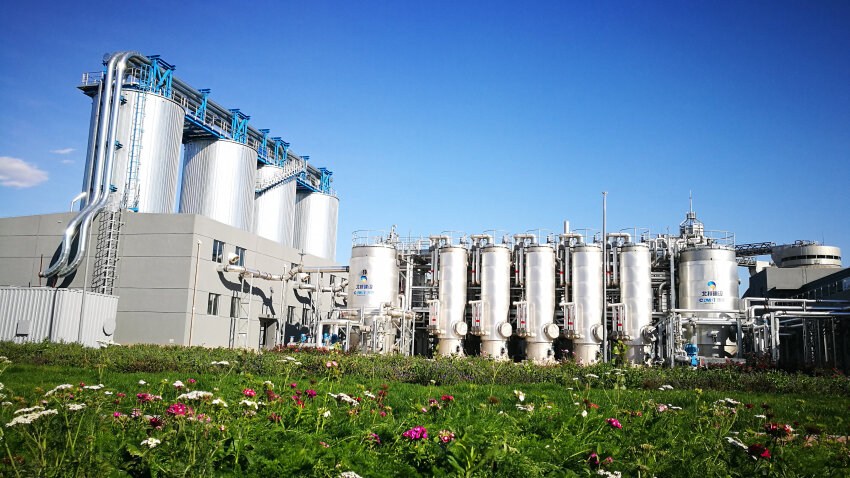 View from afar of large, cylindrical metal reactors for thermal hydrolysis treatment plant with a meadow in the foreground